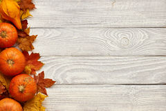 Autumn leaves and pumpkins over old wooden background Royalty Free Stock Photo