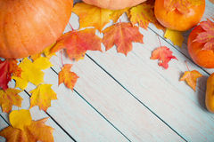 Autumn leaves and pumpkins on wooden background Royalty Free Stock Photography