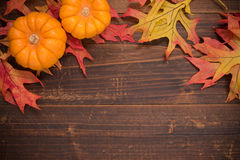 Autumn leaves  and pumpkins on a wooden background forming a bor Royalty Free Stock Photos