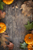 Autumn leaves and pumpkins on the wooden background Stock Photography