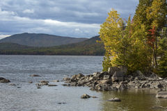 Autumn leaves on rocky shore of Flagstaff Lake, northwestern Mai. Fall foliage along the rocky shoreline of Flagstaff Lake, with mountains in the distance, in Royalty Free Stock Photos