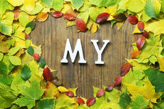 Autumn leaves in shape of heart on wooden table Royalty Free Stock Photography