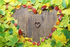 Autumn leaves in shape of heart on wooden table Royalty Free Stock Image