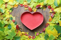 Autumn leaves in shape of heart on wooden table Royalty Free Stock Photos