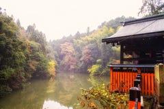 Autumn leaves and shrine in Fushimi Inari. Autumn leaves and shrine near pond with mist in morning at Fushimi Inari, Kyoto, Japan royalty free stock image