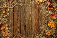 Autumn leaves and straw on wooden background Royalty Free Stock Photos