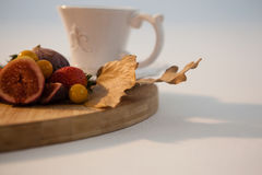 Autumn leaves, various fruits and cup of tea on chopping board Stock Photos
