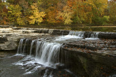 Autumn leaves and waterfall royalty free stock photography