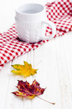 Autumn leaves with white cup. On a white wooden table Stock Images