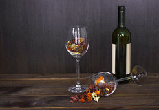 Autumn leaves in a wine glass and wine bottle on wooden table background Royalty Free Stock Image