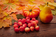 Autumn leaves on wooden table. Fruits and Royalty Free Stock Image
