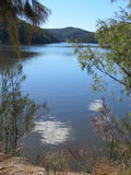 Autumn light. Sunlight sparkles on tree lined Cowan Creek in the Hawkesbury River basin in NSW royalty free stock photo
