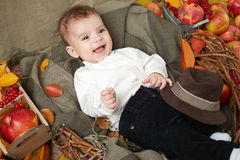 Autumn little boy lie on yellow fall leaves, apples, pumpkin and decoration on textile Royalty Free Stock Photo