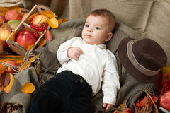 Autumn little boy lie on yellow fall leaves, apples, pumpkin and decoration on textile royalty free stock images