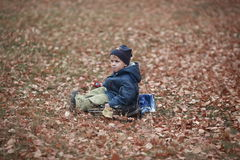 Autumn loneliness. Lonely sad boy sitting in autumn foliage royalty free stock photos