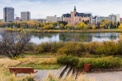 Autumn. Lonely bench by the river with a view of Saskatoon downt Stock Photo