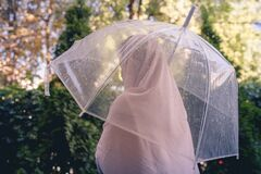 Free Autumn. Lonely Muslim Woman In A Headscarf Under A Transparent Umbrella With Rain Drops Walking In A Park, Garden. Rainy Day Royalty Free Stock Photography - 196962657