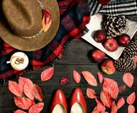 Autumn look accessories flat. Top view autumn red leaves female accessories hat shoes scarf and red apples cappuccino Stock Photo