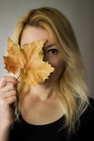 Autumn look. Blond woman hiding face behind dry leaf stock images