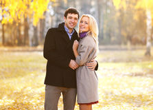 Autumn, love, relationships and people concept - beautiful couple. Autumn, love, relationships and people concept - beautiful young couple walking in sunny Royalty Free Stock Photography