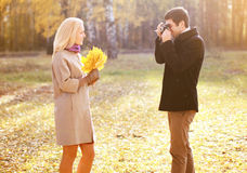 Autumn, love, relationships and people concept - happy couple. Having fun outdoors men photographing on retro vintage camera women in autumn park Stock Photography
