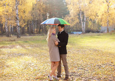 Autumn, love, relationships and people concept - lovely couple. Autumn, love, relationships and people concept - lovely young couple with colorful umbrella Stock Images