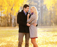 Autumn, love, relationships and people concept - lovely couple. Autumn, love, relationships and people concept - lovely young couple in love outdoors in sunny Royalty Free Stock Images