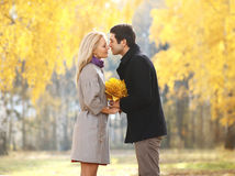 Autumn, love, relationships and people concept - pretty couple. Autumn, love, relationships and people concept - pretty young couple kissing in autumn park Stock Photo