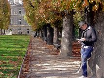 Autumn in the Luxembourg Garden. Luxembourg Garden. Man reads a book under the tree of chestnut. People enjoy sunny autumn day. Remembering Paris royalty free stock photography