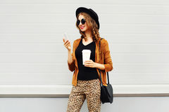 Autumn luxury look, pretty cool smiling young woman with coffee cup using smartphone walking in city, happy female model Royalty Free Stock Images