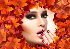 Autumn Makeup and Nail Art Trend. Fall Beauty Fashion Girl. Professional makeup and manicure. Closeup face fashion model appearing between the leaves Stock Photos