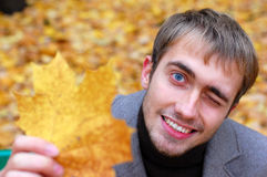 Autumn. the man. smile. park. Portrait of the smiling man with a maple leaf in park in the fall Royalty Free Stock Photo