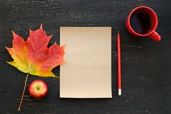 Autumn maple leaf, apple, cup of tea, paper for text and pencil Stock Photos