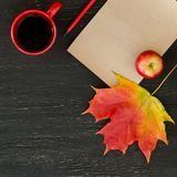 Autumn maple leaf, apple, cup of tea, paper for text and pencil Royalty Free Stock Image