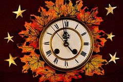 Autumn maple leaves, different colors of yellow, gold and red on the background of vintage watches, stock image