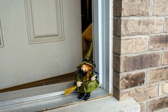 Witch on Halloween feast on the doorstep of the house Stock Photo