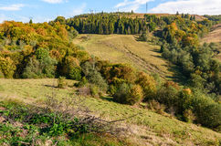 Autumn meadow on hillside of mountain range. Early autumn mountain landscape. green meadow near the forest on the hillside in Carpathians. powerlines on top of a Royalty Free Stock Image