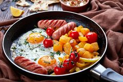 Autumn meal set on a wooden background, close up. Autumn meal set: sunny side eggs, maple glazed pumpkin, roasted sausages, tomatoes with baba ganoush dip made royalty free stock photo
