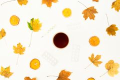 Autumn medical concept with hot tea cup, medicines, thermometer and autumn leaves on white background. Flat lay, top view. Autumn medical concept with hot tea Stock Photo
