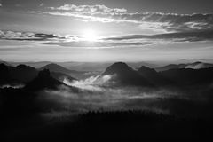 Autumn melancholy misty daybreak. Misty awakening in a beautiful hills. Peaks of hills are sticking out from foggy background Royalty Free Stock Photo