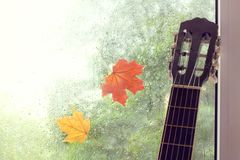 Autumn melody. Guitar against the window with a pair of adhering maple leaves and rain drops Stock Photos