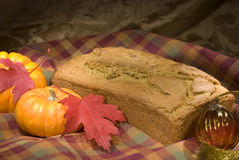 Autumn Menu - Pumpkin Bread. Autumn toned image of pumpkin bread with mini pumpkins, autumn leaves, golden glass ornament and green, red and gold autumn fabric Stock Photo