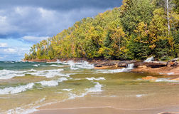 Autumn at Miners Beach. Elliot Falls (Miners Beach Falls) cascades into Lake Superior as waves break on the autumn coast of Pictured Rocks National Lakeshore in Stock Images