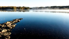 Autumn misty morning on the lake with golden lighten fog Stock Photography