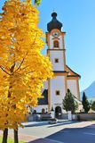 Autumn in Mittersill, Austria. Parish church. Tree with very yellow autumn leafs and the baroque parish church or Pfarrkirche of Mittersill, National Park Hohe Royalty Free Stock Photography