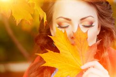 Autumn model, bright make up. woman on background fall landscape. Leaves of trees. Girl Model on autumn season. Fashion people Stock Photos