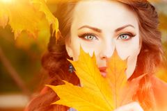 Autumn model, bright make up. woman on background fall landscape royalty free stock images