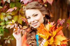 Autumn model, bright make up. woman on background fall landscape Royalty Free Stock Photos