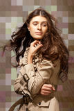Autumn mood. Young elegant woman with flowing hair on abstract checkered background Royalty Free Stock Photo