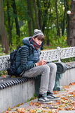 Autumn mood in autumn park. A lonely teenager sits on a bench in autumn park Stock Photo
